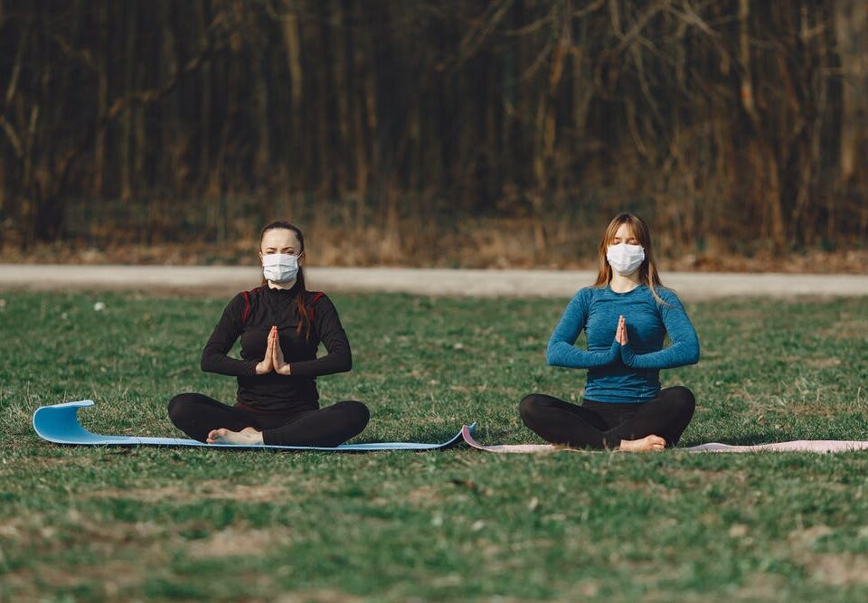 two ladies doing yoga outdoors